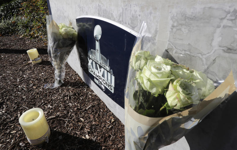 Flowers and candles rest near a sign for the Seattle Seahawks NFL football team headquarters Tuesday, Oct. 16, 2018, in Renton, Wash. in tribute to team owner Paul Allen, who died Monday, Oct. 15, 2018 in Seattle. (AP Photo/Ted S. Warren)