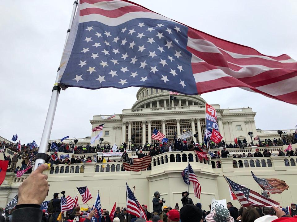 Rioters stand on the US Capitol building to protest the official election of President-elect Joe Biden on Jan. 6, 2021 on Washington DC.