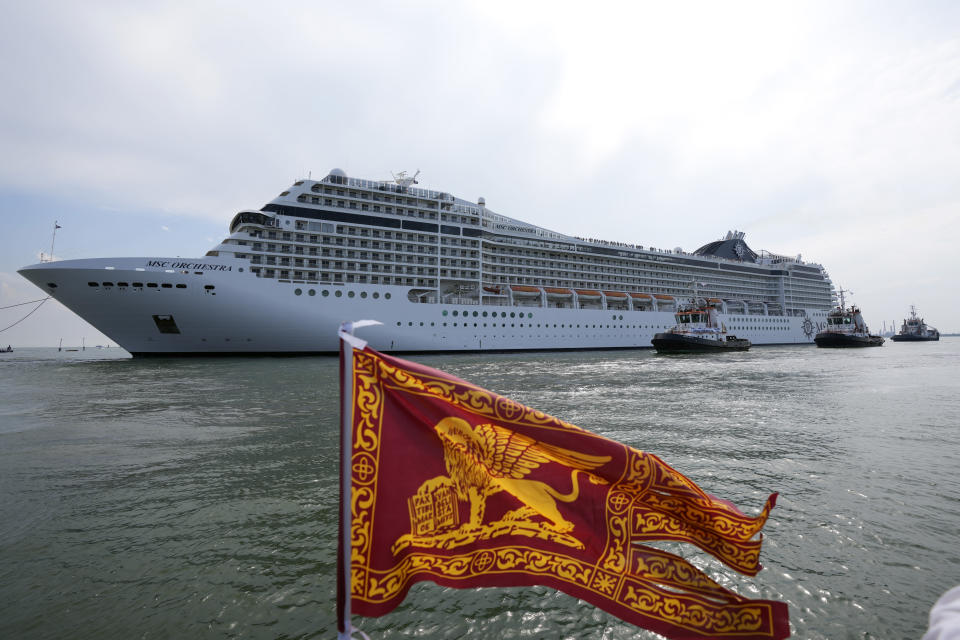 The the 92,409-ton, 16-deck MSC Orchestra cruise ship exits the lagoon as a flag of the Lion of St. Mark, the symbol of Venice, is being waved, in Venice, Italy, Saturday, June 5, 2021. The first cruise ship leaving Venice since the pandemic is set to depart Saturday amid protests by activists demanding that the enormous ships be permanently rerouted out the fragile lagoon, especially Giudecca Canal through the city's historic center, due to environmental and safety risks. (AP Photo/Antonio Calanni)