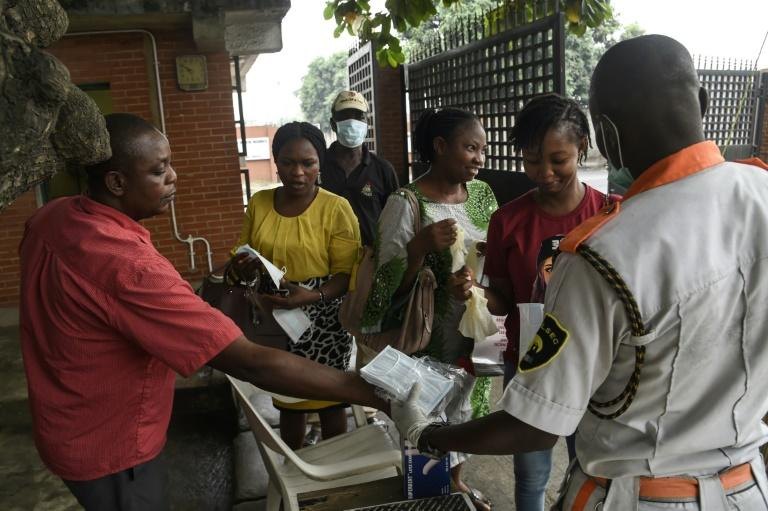 Visitors to a state hospital in Lagos collect facemasks and gloves and have their hands sanitised
