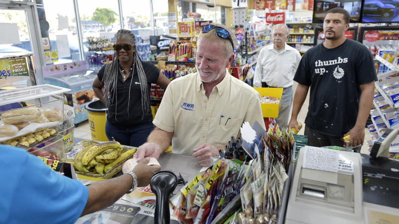 Russell Robinson buys 50 Mega Millions lottery tickets at the Kwik Stop food store at 46th Avenue and Hollywood Boulevard, in Hollywood, Fla., Friday, Oct. 19, 2018. (Michael Laughlin/South Florida Sun-Sentinel via AP)