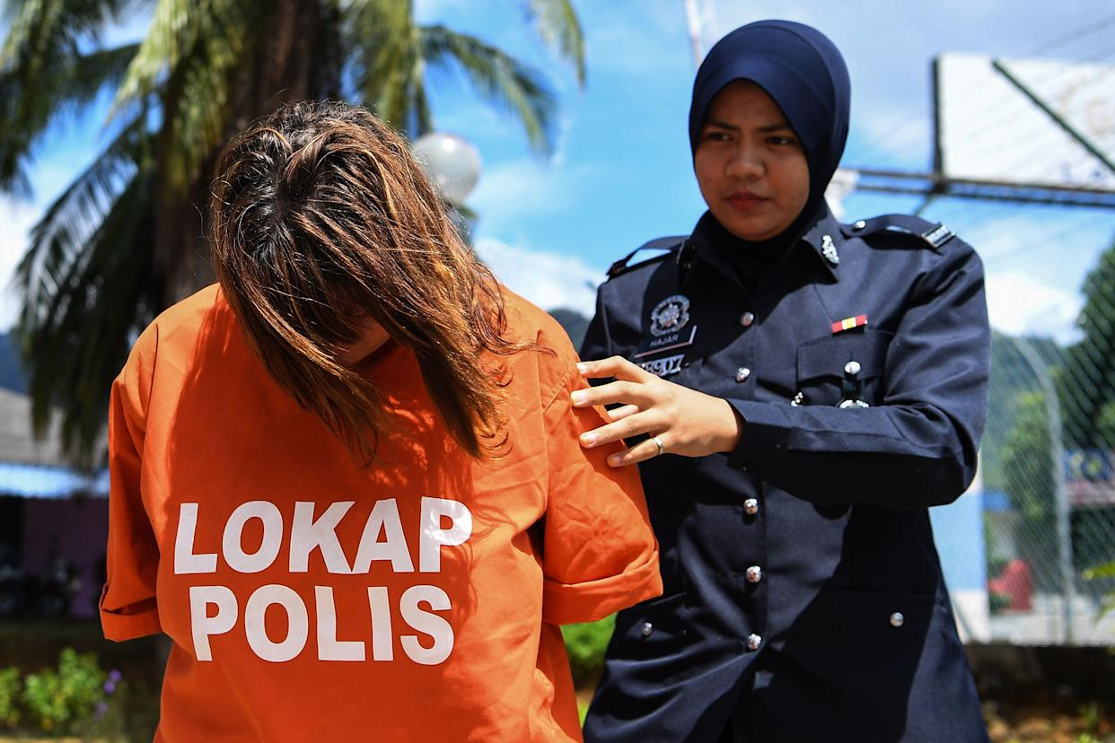 British national Samantha Jones (L) is escorted by a police officer as she arrives at a court in Langkawi on October 30, 2018. - Jones, 51, was detained after her husband John William Jones, 62, was found with a stab wound to his chest on the floor of his house on Langkawi. (Photo by Alif BAKRI / AFP)        (Photo credit should read ALIF BAKRI/AFP via Getty Images)