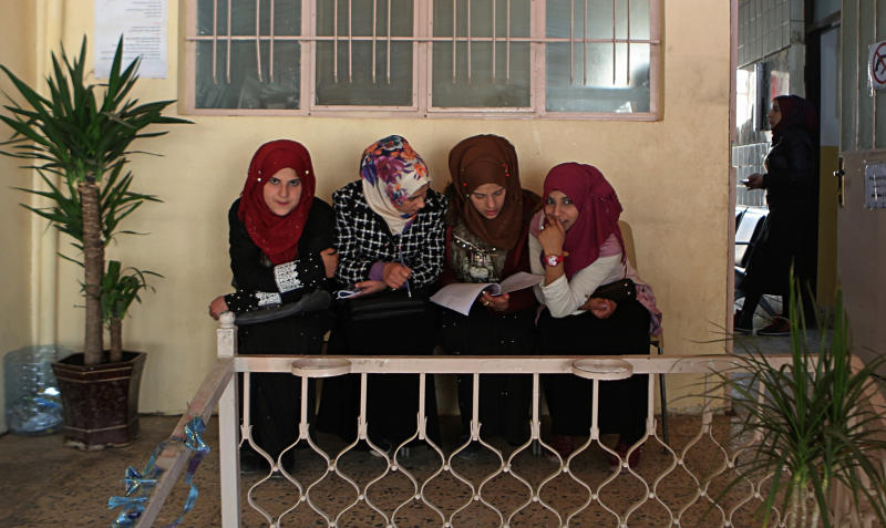In this Feb. 26, 2019 photo, women wait for legal advice in a legal clinic supported by the Norwegian Refugee Council, in west Mosul, Iraq. Thousands of Iraqi families face crushing social and legal discrimination -- all because of the choices their male relatives made under the Islamic State group's rule. They've been disowned by relatives and abandoned by the state. (AP Photo/Khalid Mohammed)