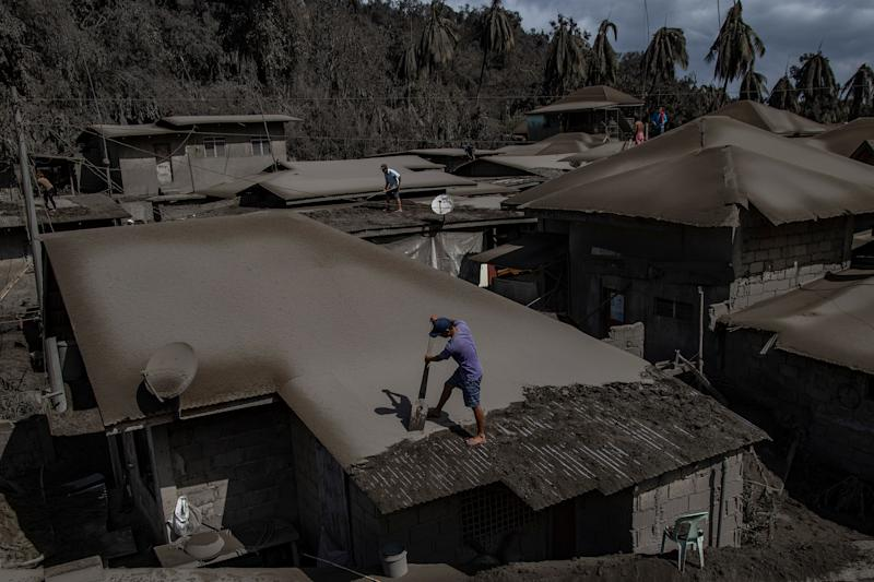 Men clean rooftops of ash from the recent eruption. | Ezra Acayan—Getty Images