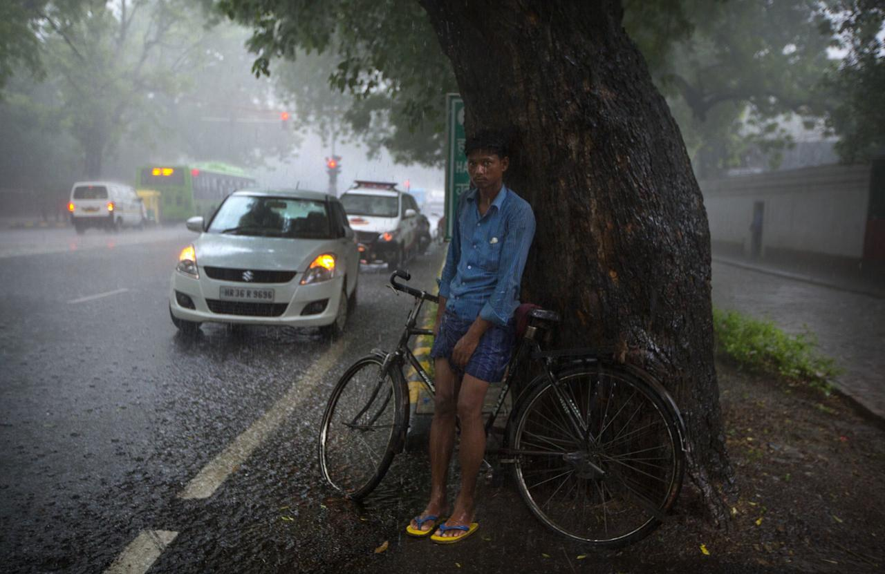 <p>A cyclist takes refuge under a tree from the pelting rain in New Delhi, India. The monsoon season in India lasts from June to September is very crucial for India's agriculture sector that accounts for more than 13 percent of the economy and provides work for about half of the country's 1.25 billion people.(AP Photo/Manish Swarup) </p>