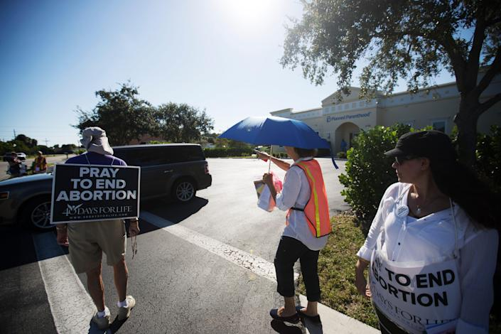 People protesting abortion offer literature to an exiting vehicle at Planned Parenthood in Fort Myers on Thursday, October 15, 2020.