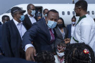 Ethiopia's Prime Minister Abiy Ahmed greets children holding flowers on his arrival at the airport, ahead of a final campaign rally, in the town of Jimma in the southwestern Oromia Region of Ethiopia Wednesday, June 16, 2021. The country is due to vote in a general election on Monday, June, 21, 2021. (AP Photo/Mulugeta Ayene)