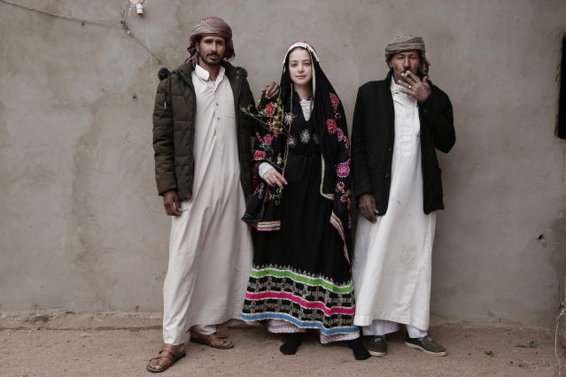 In this March 31, 2019 photo, an Egyptian student borrows a Bedouin wedding dress to pose for a photograph with Bedouin men from the Hamada tribe, in Wadi Sahw, Abu Zenima, in South Sinai, Egypt. Four Bedouin women are for the first time leading tours in Egypt's Sinai Peninsula, breaking new ground in their deeply conservative community, where women almost never work outside the home or interact with outsiders. The tourists can only be women, and the tours can't go overnight. Each day before the sun sets, the group returns to the Hamada's home village in Wadi Sahu, a narrow desert valley. (AP Photo/Nariman El-Mofty)