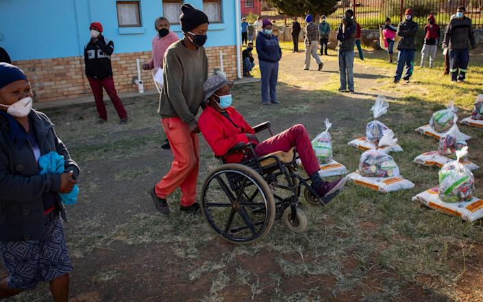 A man helps another to get his food parcel as other parishioners at the AGS Church adhere to social distancing in Graaff Reinet, South Africa - Shutterstock