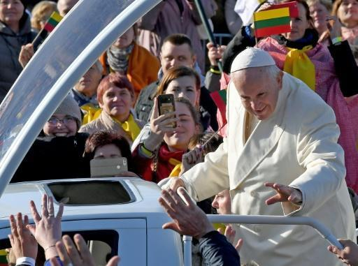 Pope Francis waves as he travels among crowds of followers in Kaunas, Lithuania