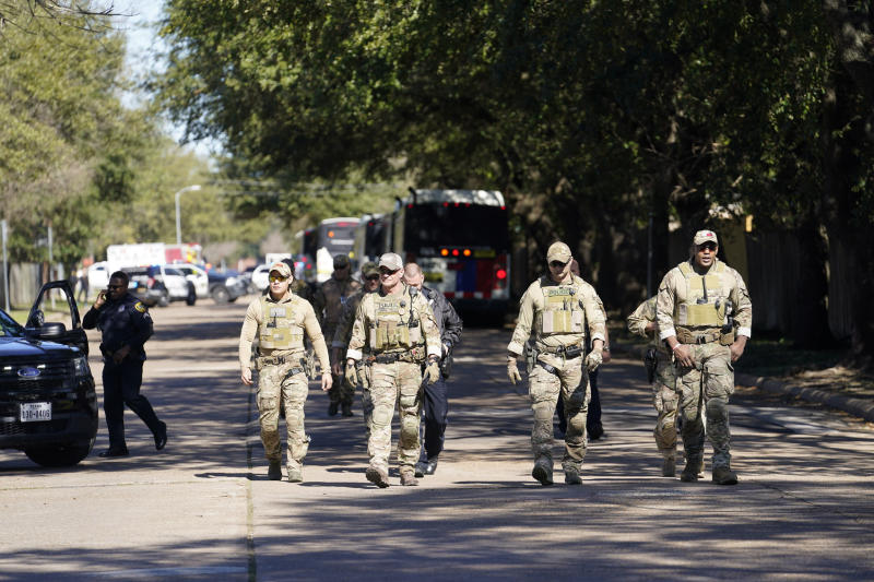 Law enforcement personnel walk along Rockcrest Rd. after an explosion occurred at nearby Watson Grinding and Manufacturing, Friday, Jan. 24, 2020, in Houston. (Melissa Phillip/Houston Chronicle via AP)