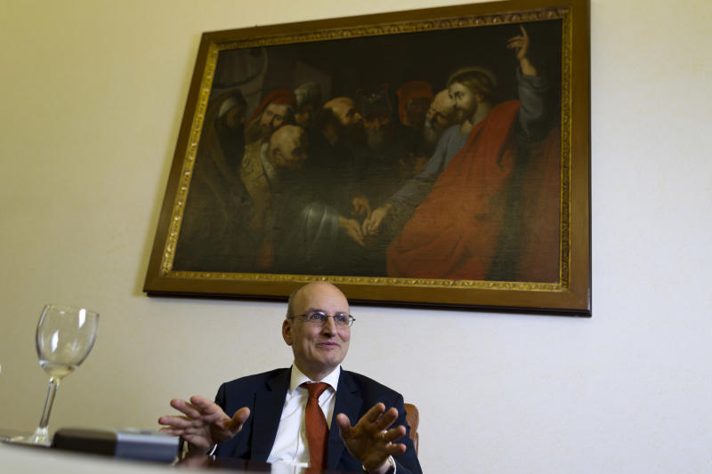 """In this picture taken on Monday, June 10, 2013, Ernst von Freyberg, president of the Vatican Bank I.O.R. (Istituto per le Opere Religiose), sits under a rendition of Peter Paul Rubens' 1612 painting """"The tribute money"""", inspired to the answer attributed to Jesus: """"Render unto Caesar the things that are Caesar's, and unto God the things that are God's"""" when he was asked wether it was right or not to pay taxes to the Romans, as he talks with the Associated Press during an interview at his office in Vatican City. The Vatican still hasn't fully solved an embarrassing shutdown in credit card services, despite announcing four months ago that systems were back up - as Pope Benedict XVI's shock resignation laid the ground for a bonanza in Vatican-minted papal memorabilia. The impact has been far worse than the Vatican ever let on, costing the Holy See a fortune at a time when the Catholic world is still buzzing with excitement about the election of Pope Francis. (AP Photo/Domenico Stinellis)"""
