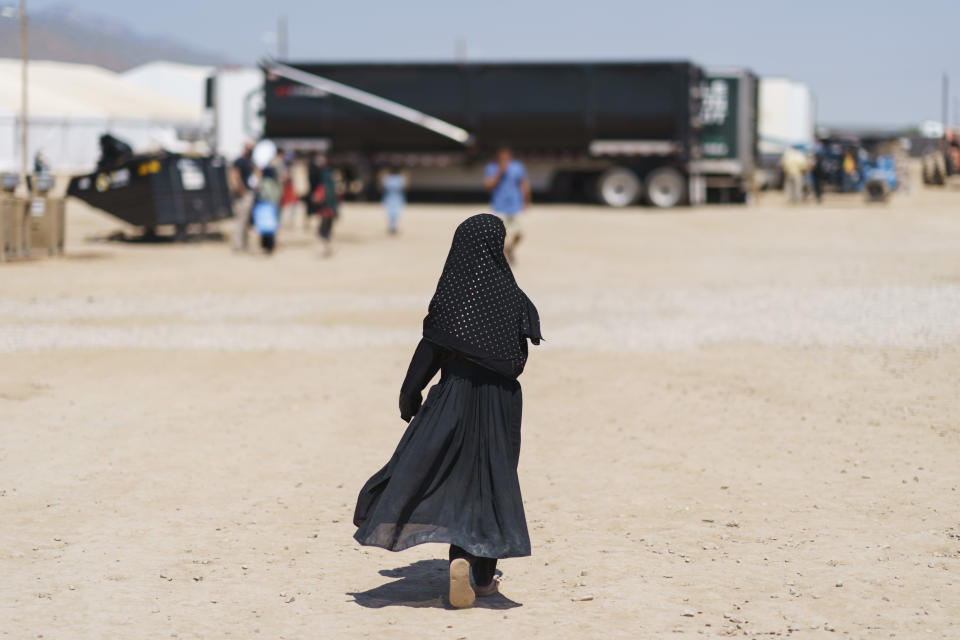 A child walks through Fort Bliss' Doña Ana Village where Afghan refugees are being housed, in New Mexico, Friday, Sept. 10, 2021. The Biden administration provided the first public look inside the U.S. military base where Afghans airlifted out of Afghanistan are screened, amid questions about how the government is caring for the refugees and vetting them. (AP Photo/David Goldman)