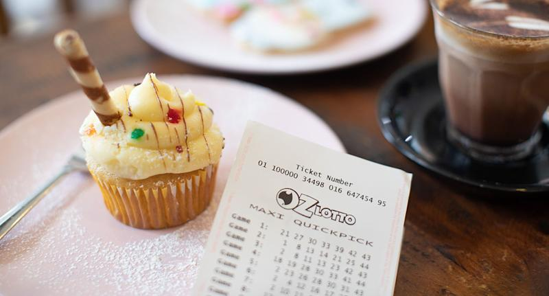 An Oz Lotto ticket sits on a plate next to a cupcake and a coffee.