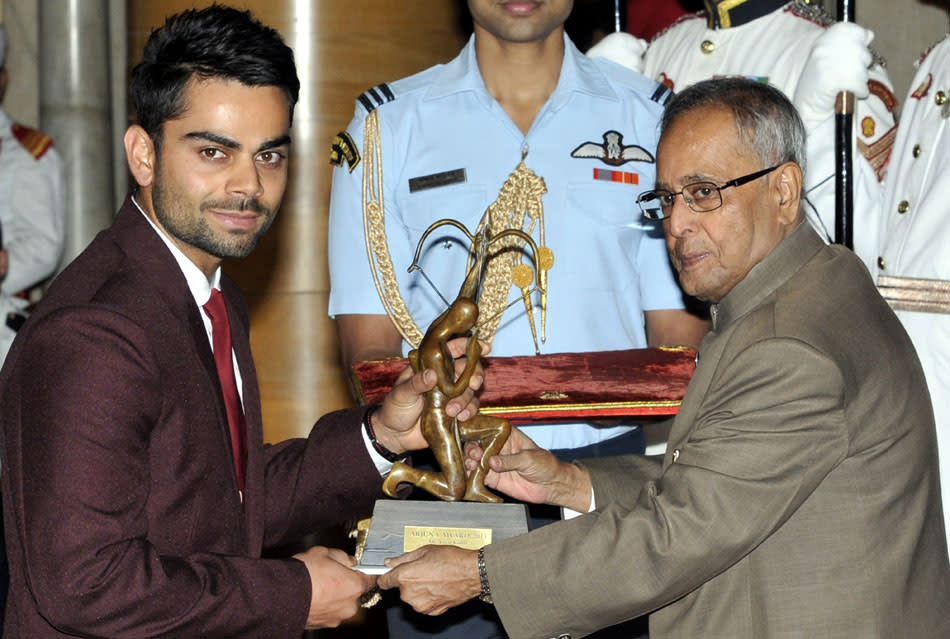 President Pranab Mukherjee honors cricketer Virat Kohli with Arjun Award during National Sports Award presentation ceremony at Rashtrapati Bhavan on August 31, 2013 in New Delhi, India. National Sports Awards were presented to the country's top athletes and coaches with shooter Ronjan Sodhi getting the country's highest sporting honour Rajiv Gandhi Khel Ratna, while cricketer Virat Kohli was among the Arjuna awardees. (Photo by Mohd Zakir/Hindustan Times via Getty Images)