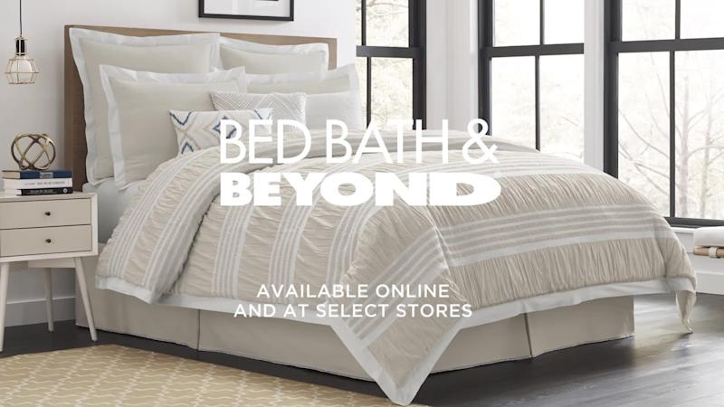 Bed with pillows and coverings in a room, with logo and promo text superimposed.
