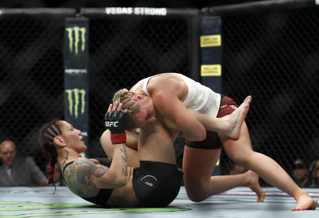 "Cris ""Cyborg"" Justino, of Brazil, is taken down by Yana Kunitskaya, of Russia, during a featherweight title mixed martial arts bout at UFC 222 on Saturday, March 3, 2018, in Las Vegas. (Steve Marcus/Las Vegas Sun via AP)"