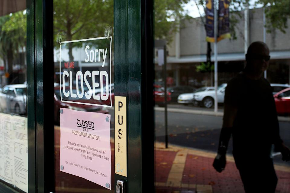 TAMWORTH, AUSTRALIA - APRIL 04: A man walks past closed retail stores along Peel Street on April 04, 2020 in Tamworth, Australia. (Photo by Lisa Maree Williams/Getty Images)