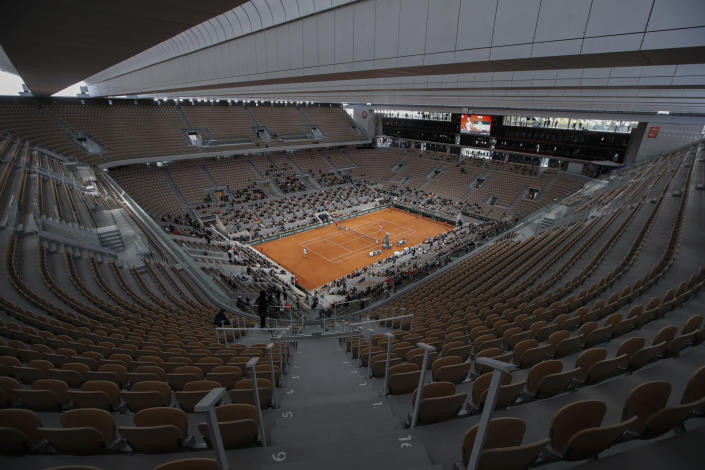 FILE - In this file photo dated Sunday, Oct. 11, 2020, rows of empty seats are seen at centre court at the Roland Garros stadium in Paris as Serbia's Novak Djokovic and Spain's Rafael Nadal warm up for the final match of the French Open tennis tournament. The 2021 French Open schedule is being disrupted by the coronavirus pandemic for the second year in a row, as organizers said Thursday April 8, 2021, the Grand Slam tournament will be delayed by one week because of surging virus cases in France.(AP Photo/Alessandra Tarantino, FILE)