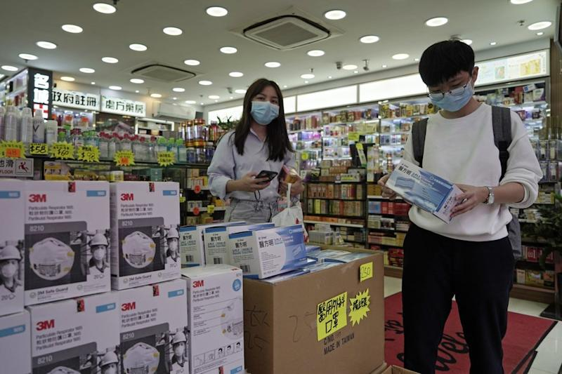 Customers purchase protective face masks at a pharmacy in Hong Kong.
