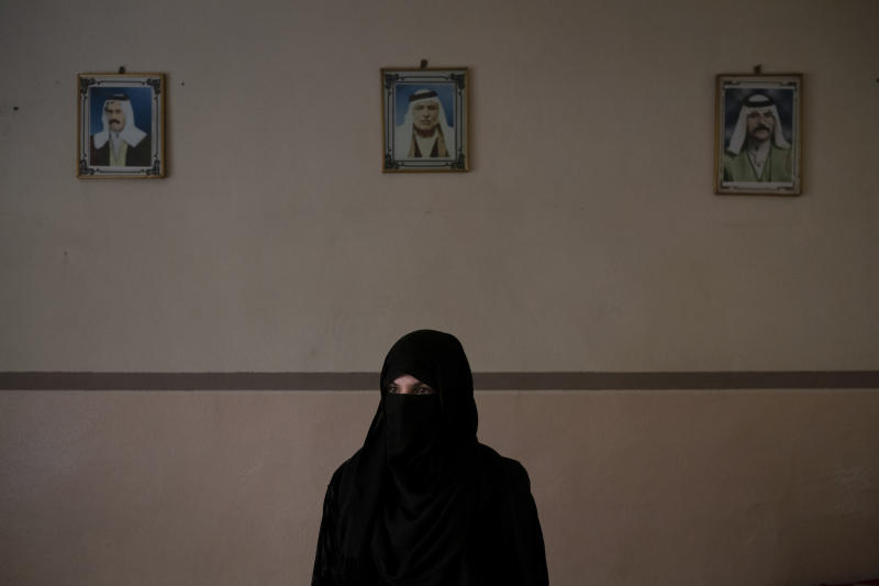 In this April 14, 2019 photo, Khadija Abd poses for a portrait in her family's house in Mosul, Iraq. On a chilly January evening, the Abd family had just finished supper at their farm when the two men with guns burst into the room. They said they were from the Iraqi army. In fact, they were Islamic State group militants who had come down from the surrounding mountains into Badoush with one thing on their mind: Revenge. (AP Photo/Felipe Dana)