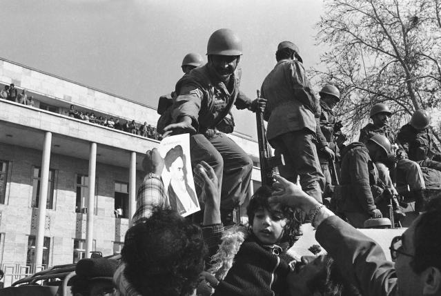 FILE - In this Jan. 15, 1979 file photo, a smiling Iranian soldier is hailed by demonstrators who decorated them with flowers and pictures of Ayatollah Ruhollah Khomeini, in Tehran, Iran. Wednesday, Jan. 16, 2019 marks the 40th anniversary of the shah abandoning his Peacock Throne and leaving his nation for the last time in his life, setting the stage for the country's 1979 Islamic Revolution only a month later. (AP Photo, File)