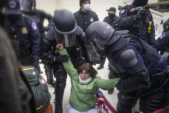 A woman is helped up by police during a rally Wednesday, Jan. 6, 2021, at the Capitol in Washington. (AP Photo/John Minchillo)