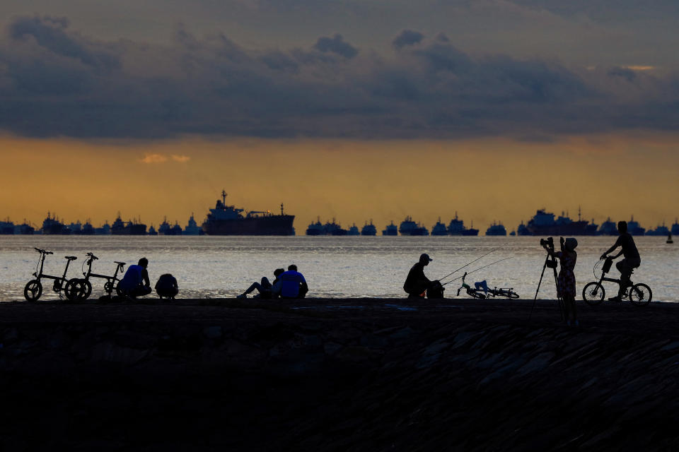 People are silhouetted at sunrise along with vessels anchored along the southern coast on May 30, 2021 in Singapore. Singapore enters a month long heightened alert from May 16 to June 13 to curb the spread of COVID-19 cases in the local community. New restrictions on movements and activities have been introduced such as limiting social interaction to two, prohibiting dining out and a reduced operating capacity at shopping malls, offices and attractions. (Photo by Suhaimi Abdullah/NurPhoto via Getty Images)