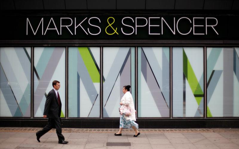 Pedestrians walk past an M&S shop in northwest London