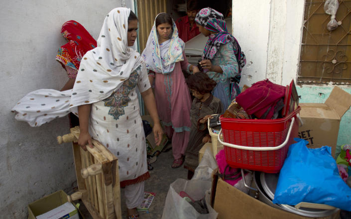 Pakistani Christian women collect their belongings to leave their home in a suburb of Islamabad, Pakistan on Thursday, Aug. 23, 2012. A Christian girl from the same locality was sent to a Pakistani prison after being accused by her furious Muslim neighbors of burning pages of the Islamic holy book, the Quran, in violation of the country's strict blasphemy laws. According to families they feel threatened and asked by Muslim house owners to vacate their houses. (AP Photo/B.K. Bangash)