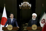 Japanese Prime Minister Shinzo Abe, left, speaks with media during a joint press conference with Iranian President Hassan Rouhani, after their meeting at the Saadabad Palace in Tehran, Iran, Wednesday, June 12, 2019. The Japanese leader is in Tehran on an mission to calm tensions between the U.S. and Iran. (AP Photo/Ebrahim Noroozi)