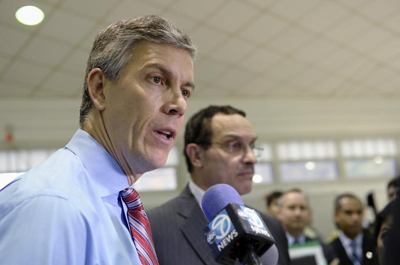 Education Secretary Arne Duncan, left, stands with Washington Mayor Vincent Gray, as he speaks to reporters during a visit to Malcolm X Elementary School in Washington, Thursday, Nov. 7, 2013. Duncan announced that today's fourth and eighth graders are doing better than their predecessors in math and reading. Today's fourth and eighth graders are doing better than their predecessors in math and reading, but despite record high scores it's too soon to start celebrating. The vast majority of students still are not demonstrating solid academic achievement in either subject, according to the Nation's Report Card, released Thursday. (AP Photo/Susan Walsh)