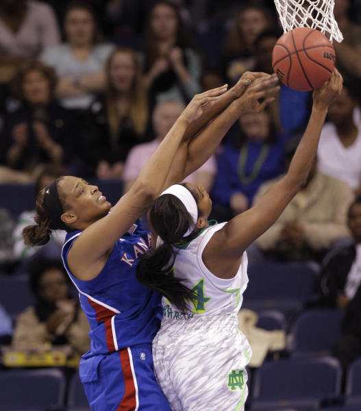 Kansas forward Carolyn Davis, left, and Notre Dame forward Ariel Braker (44) battle for a rebound during the first half of a regional semi-final of the NCAA college basketball tournament Sunday March 31, 2013, in Norfolk, Va. (AP Photo/Steve Helber)