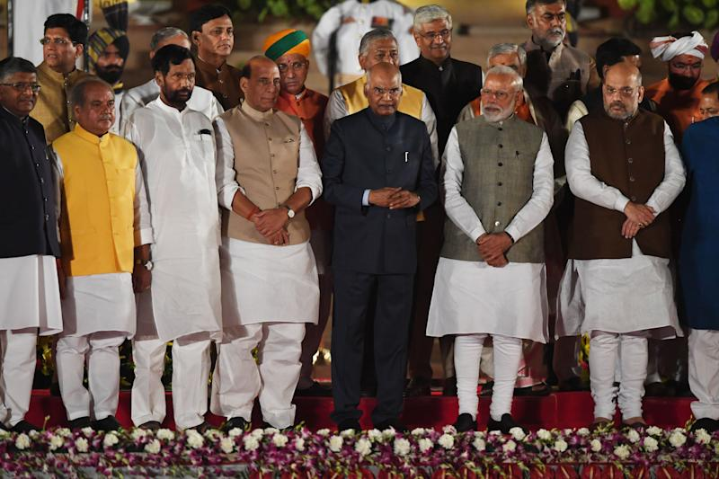 Newly sworn-in Indian Prime Minister Narendra Modi (2R) and cabinet ministers stand with President of India Ram Nath Kovind (C) after taking the oath of office at the President house in New Delhi on May 30, 2019. - India's Prime Minister Narendra Modi was sworn in Thursday in front of cheering supporters ahead of unveiling a drastically revamped Hindu nationalist government for his historic second term. Modi was the first of more than 50 cabinet ministers and deputy ministers to take the oath of office at the presidential palace in front of 8,000 people including South Asian leaders, Bollywood stars and leading political figures. (Photo by PRAKASH SINGH / AFP) (Photo credit should read PRAKASH SINGH/AFP/Getty Images)