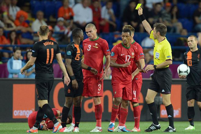 Italian referee Nicola Rizzoli (R) shows a yellow card to Dutch defender Jetro Willems (2ndL) during the Euro 2012 football championships match Portugal vs. Netherlands, on June 17, 2012 at the Metalist stadium in Kharkiv.    AFP PHOTO / PATRICK HERTZOGPATRICK HERTZOG/AFP/GettyImages