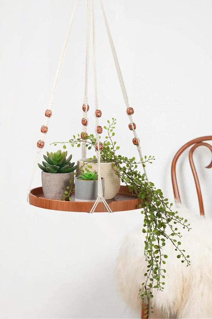 <p>Store more than one small plant with this eye-catching <span>TIMEYARD Macrame Wooden Planter Hanging Shelf</span> ($22).</p>
