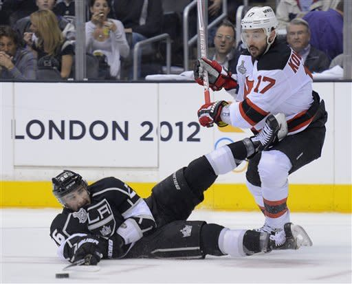 Los Angeles Kings defenseman Slava Voynov (26) reaches for the puck as he hits the ice while battling against New Jersey Devils left wing Ilya Kovalchuk (17) in the first period during Game 3 of the Stanley Cup Finals, Monday, June 4, 2012, in Los Angeles. (AP Photo/Mark J. Terrill)