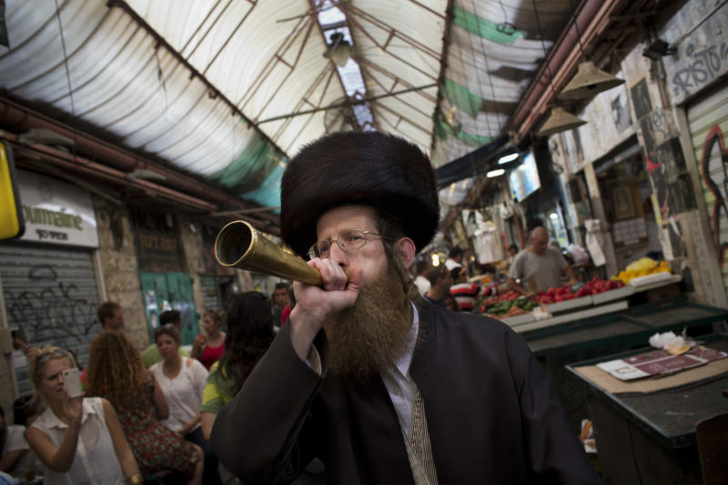 In this Oct. 12, 2012, photo an Ultra-orthodox Jewish man blows a trumpet to announce the starting of the Sabbath, Judaism's biblically-mandated day of rest, at the Mahane Yehuda market in Jerusalem. Though most Israelis are secular, Israel's founding fathers gave Judaism a formal place in the country's affairs and Ultra-Orthodox rabbis strictly govern Jewish practices such as weddings, divorces, and burials. The Ultra-Orthodox are also perennial kingmakers in Israeli coalition politics, though they make up only ten percent of the country's population. (AP Photo/Bernat Armangue)