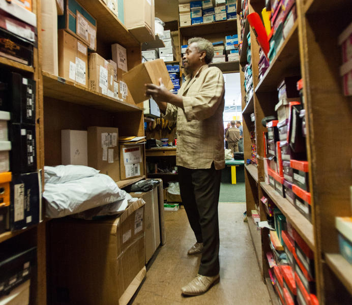 This 2014 photo provided by UPS shows a Bronx borough of New York shoe store owner placing a package in a secure location inside his shop. The Access Point is one service UPS offers to help manage the flow of delivery packages. (UPS via AP)