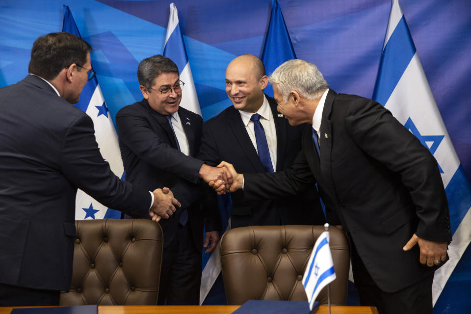 Israeli Prime Minister Naftali Bennett, second right, shakes hands with Honduran Foreign Minister Lisandro Rosales as Honduran President Juan Orlando Hernandez, second left, shakes hands with Israeli Foreign Minister Yair Lapid, after signing agreements between their two countries, at the prime minister's office, in Jerusalem, Thursday, June 24, 2021. (Heidi Levine/Pool via AP).