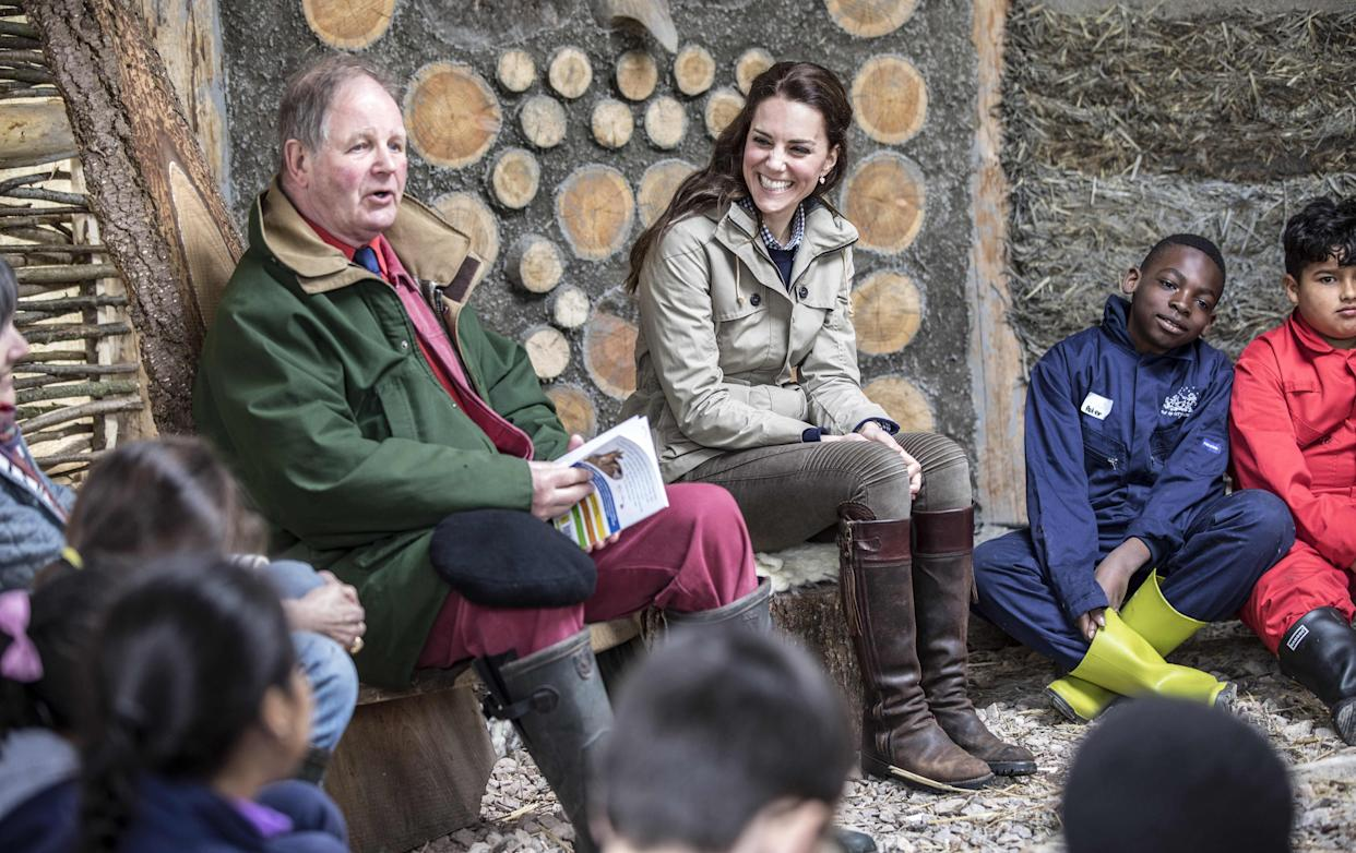Britain's Catherine, Duchess of Cambridge listens to children's author Michael Morpurgo read one of his stories to children from London's Vauxhall Primary school  during a visit to a 'Farms for Children' farm in Gloucestershire on May 3, 2017.  / AFP PHOTO / POOL / RICHARD POHLE        (Photo credit should read RICHARD POHLE/AFP via Getty Images)