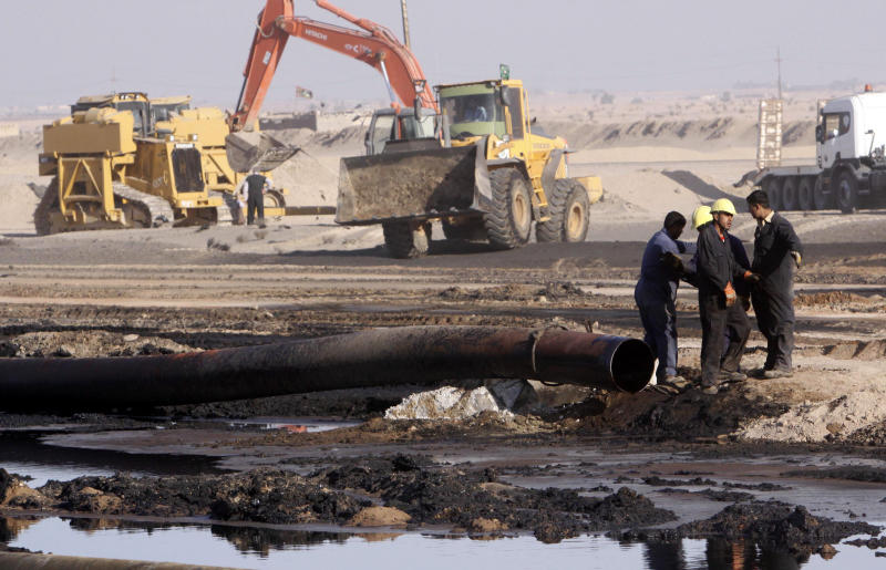 FILE - In this Dec. 14, 2011 file photo, workers repair oil pipelines at Rumaila oil fields, near the southern Iraqi city of Basra. Iraq is rich in oil, but protesters say they don't see the fruits of this wealth. Fueling the unrest, which began on Oct. 1, 2019, is anger over an economy flush with oil money that has failed to bring jobs or improvements to the lives of young people, who are the majority of those taking to the streets. (AP Photo/Nabil al-Jurani, File)