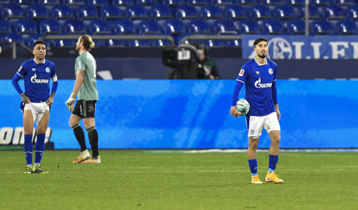 Schalke's Suat Serdar, right, takes the ball after Freiburg scored their second goal during the German Bundesliga soccer match between FC Schalke 04 and SC Freiburg at the Arena in Gelsenkirchen, Germany, Wednesday, Dec. 16, 2020. (AP Photo/Martin Meissner, Pool)