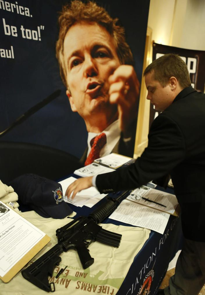 The image of Senator Rand Paul (R-KY) hangs over a M16 replica on display at a gun rights supporter sign up table at the Liberty Political Action Conference (LPAC ) in Chantilly, Virginia September 19, 2013. REUTERS/Kevin Lamarque (UNITED STATES - Tags: POLITICS)