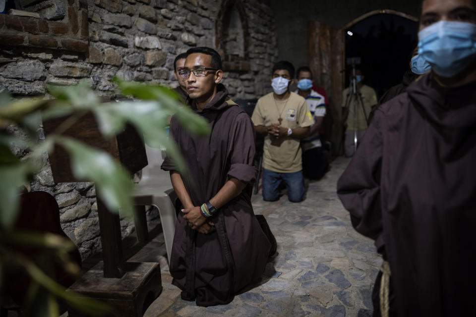Seminarist Oveniel Garcia, 21, left, kneels during a Mass celebrated by Friar Leopoldo Serrano in the chapel at Mission San Francisco de Asis, Honduras, Saturday, June 19, 2021. Garcia, a former drug addict and trafficker, entered the rehab center at the mission run by Serrano. Over the years, he became Serrano's right-hand man. (AP Photo/Rodrigo Abd)