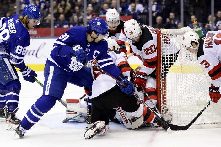 New Jersey Devils goaltender Cory Schneider (35) gets swarmed as Toronto Maple Leafs center John Tavares (91) vies for control of the puck with Devils' Blake Coleman (20) and Nico Hischier (13) while Maple Leafs right wing William Nylander (88) and Devils' Damon Severson (28) watch during the second period of an NHL hockey game Tuesday, Jan. 14, 2020, in Toronto. (Frank Gunn/The Canadian Press via AP)