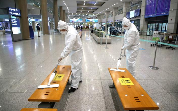 Workers wearing PPE disinfect chairs at the arrival hall of the Incheon International Airport in South Korea - Kim Sun-woong