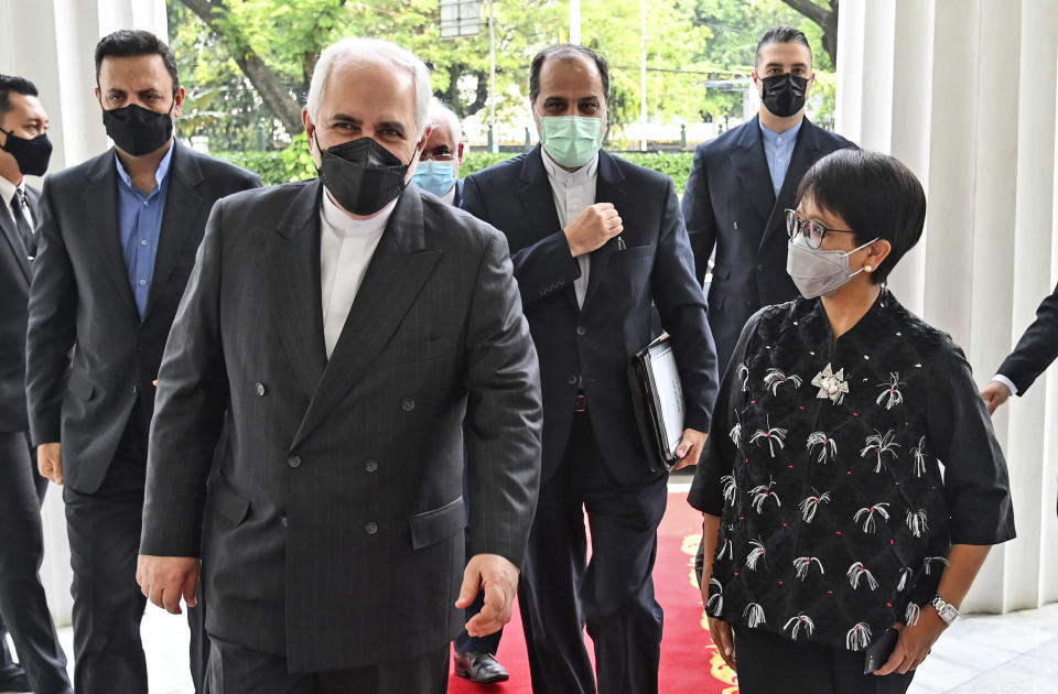 In this photo released by Indonesian Ministry of Foreign Affairs, Indonesian Foreign Minister Retno Marsudi, right, walks with her Iranian counterpart Mohammad Javad Zarif during their meeting in Jakarta, Indonesia, Monday, April 19, 2021. (Indonesian Ministry of Foreign Affairs via AP)