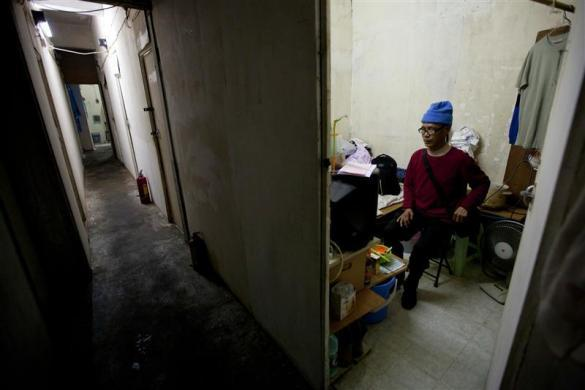 Ng, a 60-year-old man, poses for photos in his 60-square-feet (5.6-square-meters) subdivided flat inside an industrial building in Hong Kong January 19, 2012. Ng pays a monthly rent of HK$1,250 ($161) for the flat. A total of 38 residents staged an ongoing protest against the government's decision urging them to leave due to illegal subdivision in the industrial building for residential purposes, without providing them a place to stay, according to a local newspaper. Amid a slumping property market, Hong Kong is still one of the most expensive cities for buying flats.