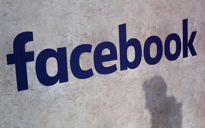 A man walking by the Facebook logo